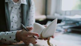 Mujer que hace medidas de las muestras para los zapatos futuros con la cinta métrica que se sienta en la tabla Primer de manos fe metrajes