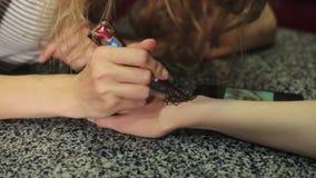 Mujer que hace mehendi floral en una mano con alheña en una tabla metrajes