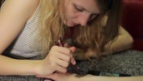 Mujer que hace mehendi floral en una mano con alheña en una tabla almacen de metraje de vídeo