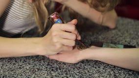 Mujer que hace mehendi floral en una mano con alheña en una tabla almacen de video