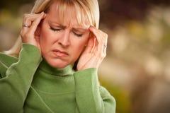 Mujer que hace muecas que sufre un dolor de cabeza Imagen de archivo libre de regalías