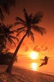 Mujer que hace pivotar en una puesta del sol Fotografía de archivo