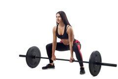 Mujer que hace posición en cuclillas con el barbell imagenes de archivo