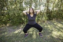 Mujer que hace posiciones en cuclillas Imagenes de archivo