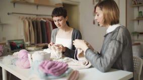 Mujer que hace punto dos que trabaja en taller de la materia textil Manos que hacen punto de la afición de la mujer