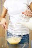 Mujer que hace que la huevo-y-leche sacude Imagenes de archivo
