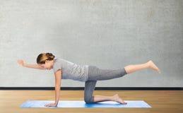Mujer que hace que la yoga en equilibrio tabla presenta en la estera Imágenes de archivo libres de regalías