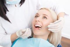 Mujer que hace que sus dientes sean examinados por el dentista fotografía de archivo libre de regalías