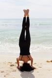Mujer que hace un headstand en la playa Imágenes de archivo libres de regalías