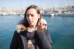 Mujer que hace un masaje de la voz en el teléfono fotografía de archivo libre de regalías
