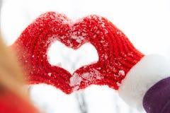 Mujer que hace un símbolo del corazón con las manos de la nieve en guantes rojos Imagen de archivo libre de regalías