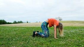 Mujer que hace un sistema de ejercicios de la yoga - estira en la hierba en un parque de la ciudad en naturaleza almacen de metraje de vídeo