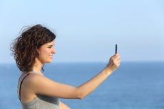 Mujer que hace una fotografía con un teléfono móvil Foto de archivo libre de regalías