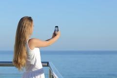 Mujer que hace una fotografía del mar con un teléfono elegante Imágenes de archivo libres de regalías