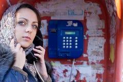 Mujer que hace una llamada telefónica pública Imagen de archivo libre de regalías