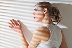 Mujer que hace una pausa la ventana con las persianas Imagen de archivo libre de regalías