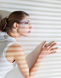 Mujer que hace una pausa la ventana con las persianas Foto de archivo libre de regalías