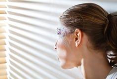 Mujer que hace una pausa la ventana con las persianas Fotos de archivo