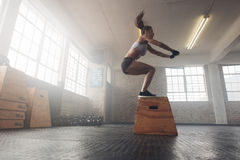 Mujer que hace una posición en cuclillas de la caja en el gimnasio Fotografía de archivo