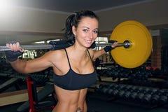 Mujer que hace una posición en cuclillas del barbell en el gimnasio Foto de archivo