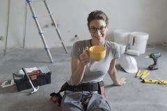 Mujer que hace una renovación casera y que tiene un descanso para tomar café fotos de archivo libres de regalías
