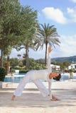 Mujer que hace yoga al lado de piscina Fotografía de archivo libre de regalías