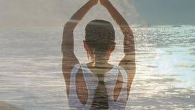 Mujer que hace yoga al lado del océano almacen de metraje de vídeo