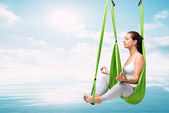 Mujer que hace yoga antigravedad aérea sobre el lago Imagenes de archivo