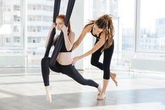Mujer que hace yoga antigravedad con ayuda del instructor personal foto de archivo