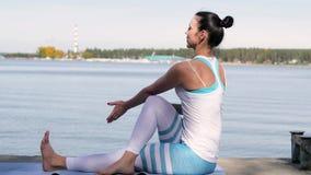 Mujer que hace yoga cerca del agua en el embarcadero Yoga en naturaleza almacen de video