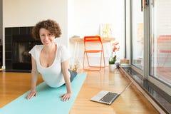 Mujer que hace yoga con el app en línea en el ordenador en su sala de estar imágenes de archivo libres de regalías
