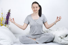 Mujer que hace yoga en cama Fotos de archivo