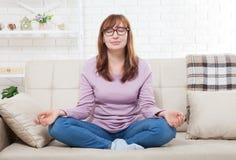 Mujer que hace yoga en casa en el dormitorio Hembra de la Edad Media que medita dentro Mujer que hace yoga concepto de la forma d fotografía de archivo libre de regalías