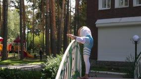Mujer que hace yoga en el parque en el puente Forma de vida sana almacen de metraje de vídeo