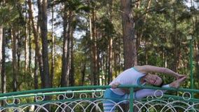 Mujer que hace yoga en el parque en el puente Forma de vida sana metrajes