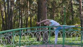 Mujer que hace yoga en el parque en el puente Forma de vida sana almacen de video