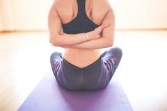 Mujer que hace yoga en el piso de madera Imagenes de archivo