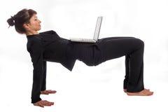 Mujer que hace yoga en el trabajo. Imagen de archivo