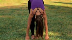 Mujer que hace yoga en hierba verde almacen de metraje de vídeo