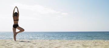 Mujer que hace yoga en la playa Imágenes de archivo libres de regalías
