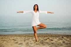 Mujer que hace yoga en la playa Fotografía de archivo