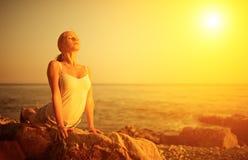 Mujer que hace yoga en la playa en la puesta del sol Imagen de archivo