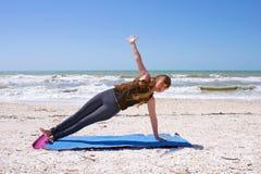 Mujer que hace yoga en la playa en tablón lateral Fotos de archivo