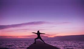 Mujer que hace yoga en la playa en surise foto de archivo