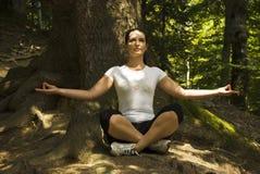 Mujer que hace yoga en la posición de loto al aire libre Fotos de archivo libres de regalías
