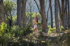 Mujer que hace yoga en un bosque con los árboles en el fondo imágenes de archivo libres de regalías