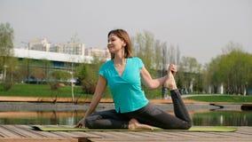Mujer que hace yoga o deporte por la charca, al aire libre almacen de video