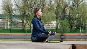 Mujer que hace yoga por la charca, al aire libre almacen de metraje de vídeo