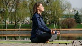 Mujer que hace yoga por la charca, al aire libre metrajes