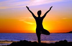 Mujer que hace yoga sobre el océano imagenes de archivo
